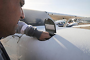 Pilot perform a preflight check on a cessna skyhawk checking the oil with a dipstick