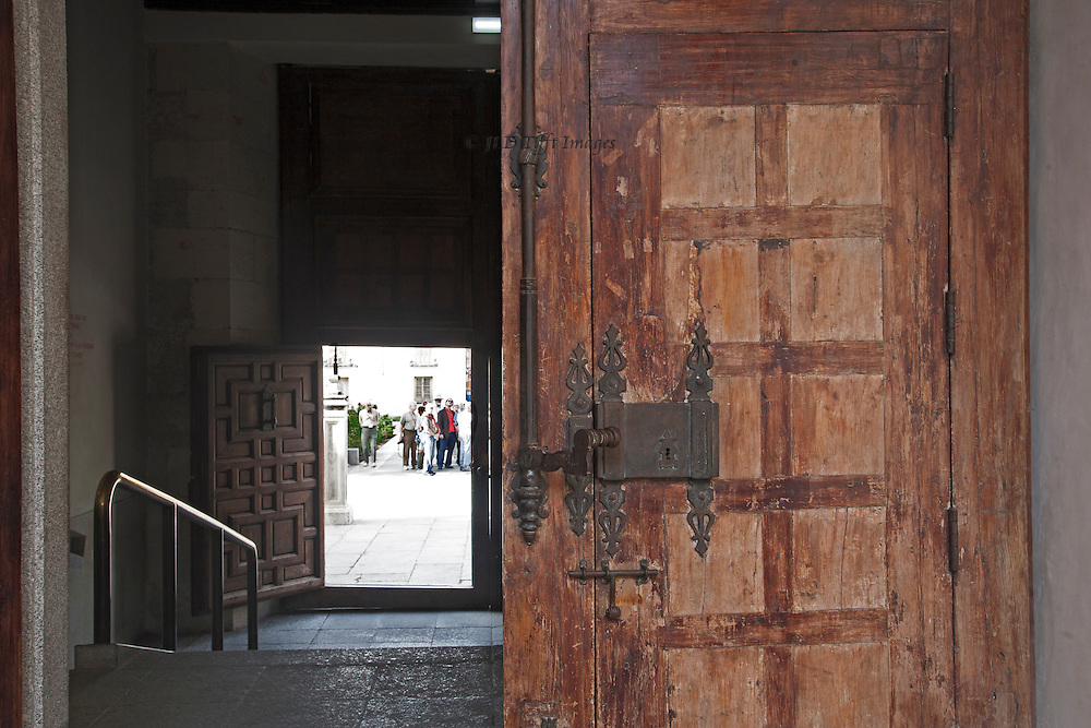 Door to the College of San Ildefonso at Alcala Henares, seen partly closed, with another doorway beyond and a group of people outside.