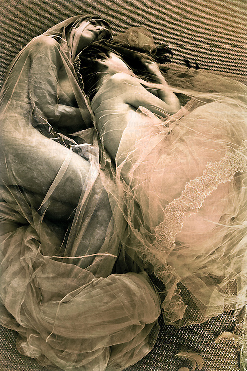 Two young women lying together under gauze material