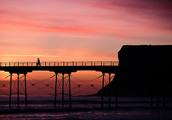 © Licensed to London News Pictures. <br /> 26/03/20167. <br /> Saltburn by the Sea, UK.  <br /> <br /> A fisherman walks along the pier as a spectacular sunrise starts the day over the beach in Saltburn by the Sea.<br /> <br /> Photo credit: Ian Forsyth/LNP