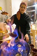 SANTIAGO DE COMPOSTELA, SPAIN - 12th of October 2017 - A lady performs the traditional culinary ritual of the Galician Queimada spell in Santiago de Compostela. Rooted in Celtic tradition, the flaming queimada drink of Galicia is believed to ward off evil spirits. Galicia, Spain.