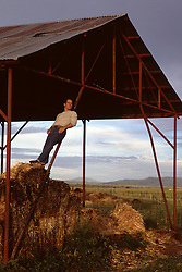 man leaning on a barn post on a ranch in New Mexico