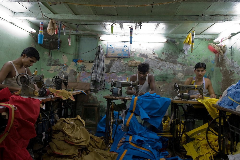 young men work at a basement tailoring shop. The average daily wages in Dharavi is Rs 80 (less than $2) a day.