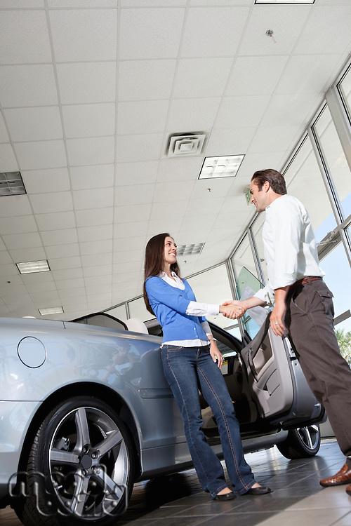 Car salesman shaking hands with female customer in showroom