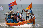 Young Indian men on boat trip celebrating Hindu Holi festival of colours at Nariman Point in Mumbai, formerly Bombay, India