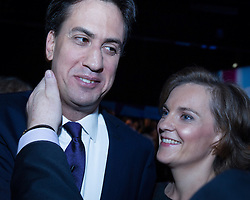 © Licensed to London News Pictures . 24/09/2013 . Brighton , UK . The Labour Party Leader , Ed Miliband , with his wife , Justine Thornton , is patted on the back of his neck by a member of the audience after delivering the Leader's Speech to the conference , this afternoon (24th September 2013) . Day 3 of the Labour Party Conference in Brighton . Photo credit : Joel Goodman/LNP