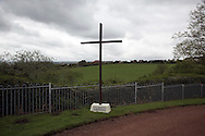 'Untitled, 2014' from the project 'The Fall and Rise of Ravenscraig' by photographer Colin McPherson.<br /> <br /> The photograph shows a cross situated within the Carfin Grotto, a place of pilgrimage for Roman Catholics, located next to the site of the former Ravenscraig steelworks.<br /> <br /> This project, photographed in 2014, looks at the topography of the post-industrial landscape at Ravenscraig, the site until its closure in 1992 of the largest hot strip steel mill in western Europe. In its current state, Ravenscraig is one of the largest derelict sites in Europe measuring over 1,125 acres (4.55 km2) in size, an area equivalent to 700 football pitches or twice the size of Monaco. It is currently being developed with a mix of housing, retail and the home of South Lanarkshire College and the Ravenscraig Regional Sports Facility.