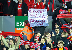 LIVERPOOL, ENGLAND - Sunday, December 13, 2009: Liverpool supporters on the Spion Kop hold up a banner reading 'Blessed by Shanks, Cursed by Yanks' in protest at the ownership by two Americam's who have saddles the club with huge debt during the Premiership match against Arsenal at Anfield. (Photo by: David Rawcliffe/Propaganda)
