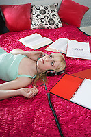 Teenage girl (16-17) listening music on bed surrounded by books
