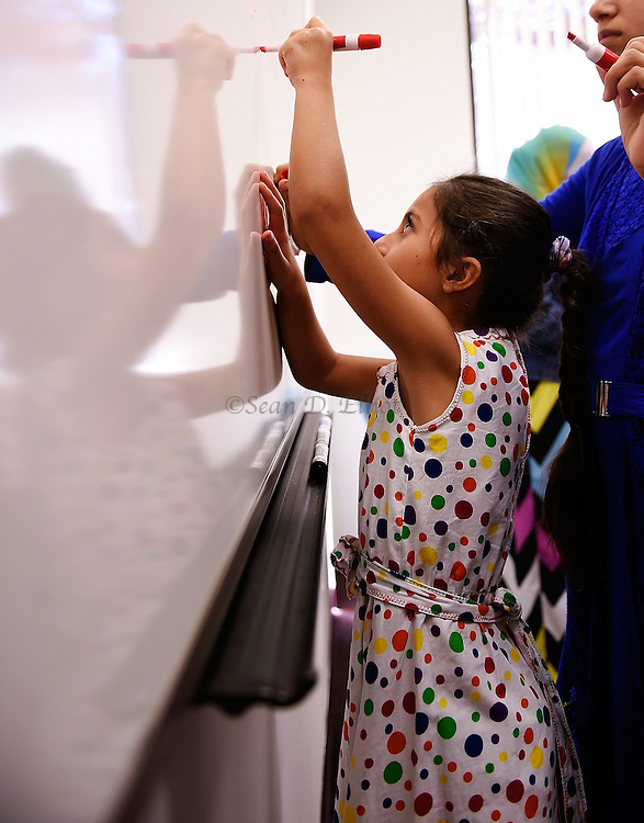 1005612433 :: 7/27/16 :: REGION :: LYNCH :: Fulla Mahmoud, 7, writes on the board in English lessons at New London Adult and Continuing Education Wednesday, July 27, 2016. Hasan Mahmoud and Fahima Jemmo and their children Fidan, 17, Hanif, 15 and Fulla, 7, are refugees from the conflict in Syria and lived for three years in Turkey before finally receiving approval to come to the United States. (Sean D. Elliot/The Day)