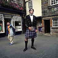 Scottish DJ, Andy Niven, wearing a Prince Charlie kilt from 21st Century Kilts, on Edinburgh's Royal Mile, Scotland, UK..