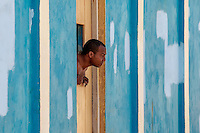 Peek-a-boo: Our views of the world are often formed or restricted by our living space and it always struck me as sad that Cubans often view the world from very small openings in their homes' windows or doors, as illustrated by this man peeking out to gaze out on the world, Baracoa Cuba.