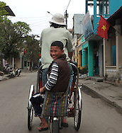 An old brother gives his younger brother a ride on a pedicab in Hue, Vietnam, Photograph by Dennis Brack