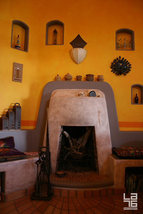 Fire place, shown as a part of a living room, colored in warm yellow and orange colors. Interior decoration by feng shui rules. The home is a beach front home in Los Barriles, Baja California Sur. <br /> <br /> Photo is part of set of photographs of a beach front home in Los Barriles, Baja California Sur, Mexico.