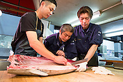 Hideto Takeda, Katsuhiki Kashima and Masakazu Sato are cutting the tuna at the wholesaler Maguro Naito at the Tsukiji Market, Tokyo, Japan.