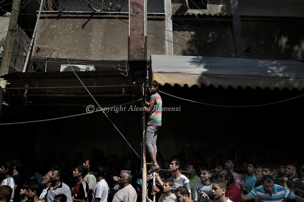 Gaza Strip, Nuseirat: Palestinians gather around the destroyed by Israeli airstrike Al-Qassam mosque in Nuseirat as rescuers look for survivors among the rubble, on August 9, 2012. ALESSIO ROMENZI