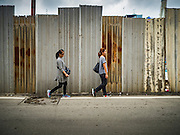 21 SEPTEMBER 2016 - BANGKOK, THAILAND: Women walk past the fence the encloses the construction site at the old Bang Chak Market. The market closed permanently on January 4, 2016. The Bang Chak Market served the community around Sois 91-97 on Sukhumvit Road in the Bangkok suburbs. Bangkok city authorities put up notices in late November 2015 that the market would be closed by January 1, 2016 and redevelopment would start shortly after that. Market vendors said condominiums are being built on the land.      PHOTO BY JACK KURTZ