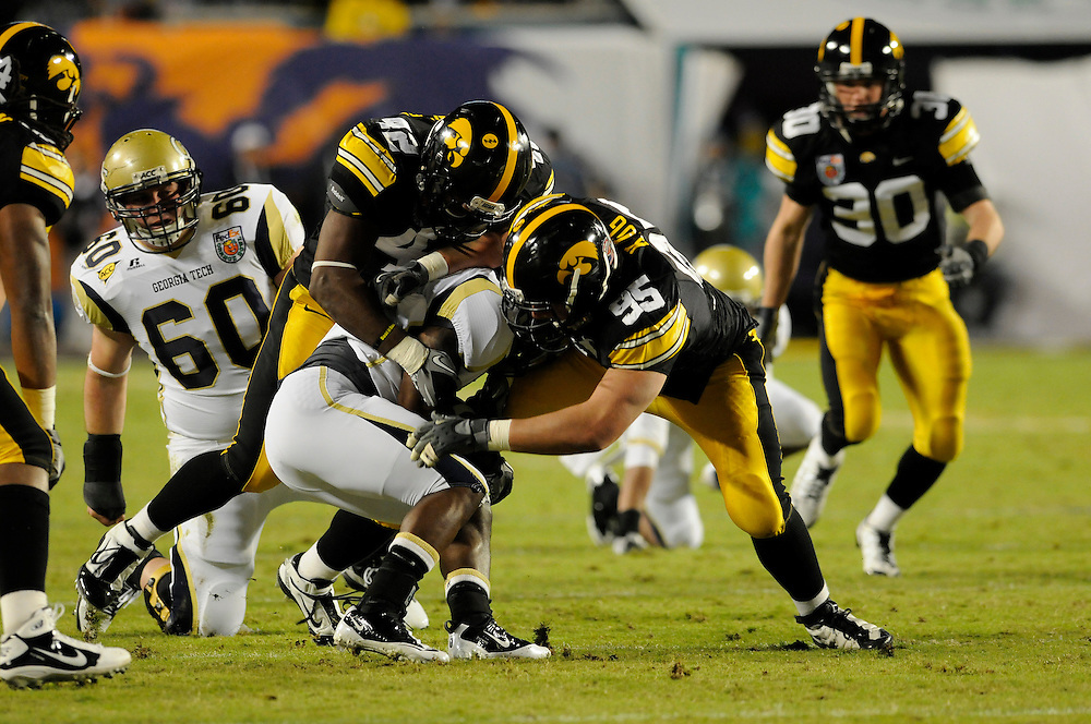 January 5, 2010: Defensive end Karl Klug (95) and linebacker Jeremiha Hunter (42) of the Iowa Hawkeyes tackle running back Marcus Wright of the Georgia Tech Yellow Jackets during the NCAA football game between the Georgia Tech Yellow Jackets and the Iowa Hawkeyes in the Orange Bowl. The Hawkeyes were leading the Yellow Jackets 14-7 at halftime.