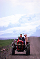 A father and his daughter riding down a dirt road (with a massive glacier in the background) in Southeast Iceland