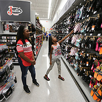 Sanyia Hamilton, 10, left, and Jayden Lauderdale, 11, look at slides and other items to spend their $100 gift cards on at Academy Sports in Tupelo Wednesday morning.