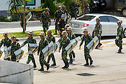 "20 MAY 2104 - BANGKOK, THAILAND:   Thai soldiers carry their riot shields while they to take up positions at the Army Club to prevent protestors from entering the club grounds after the declaration of martial law. The Thai Army declared martial law throughout Thailand in response to growing political tensions between anti-government protests led by Suthep Thaugsuban and pro-government protests led by the ""Red Shirts"" who support ousted Prime Minister Yingluck Shinawatra. Despite the declaration of martial law, daily life went on in Bangkok in a normal fashion. There were small isolated protests against martial law, which some Thais called a coup, but there was no violence.  PHOTO BY JACK KURTZ"