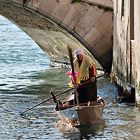 VENICE, ITALY - JANUARY 06:  A rover sails along one of the Venice canals towards the racing line ahead of the 34th  Befana Regata on January 6, 2012 in Venice, Italy.  In Italian folklore, Befana is an old woman who delivers gifts to children throughout Italy on the feast of the Epiphany on January 6 in a similar way to Saint Nicholas or Santa Claus.