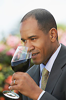 Elegant man tasting red wine close up