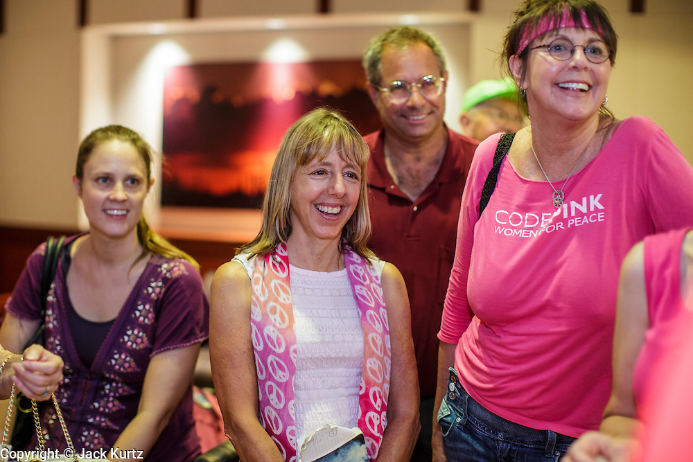 "31 JULY 2012 - PHOENIX, AZ:  MEDEA BENJAMIN, center, and other members of Code Pink, wait in the lobby of the governor's office at the Arizona State Capitol Tuesday. Medea is a political activist, best known for co-founding Code Pink and, along with her husband, activist and author Kevin Danaher, the fair trade advocacy group Global Exchange. She was also a Green Party candidate in 2000 for the United States Senate. She appeared in Phoenix to promote her new book, ""Drone Warfare: Killing by Remote Control."" She, and other members of Code Pink, presented a letter to Arizona Gov. Jan Brewer protesting Brewer's request to use the state's airspace to train drone pilots.  PHOTO BY JACK KURTZ"