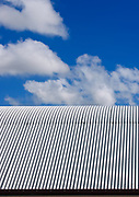 Blue sky and clouds over a corrugated tin roof.