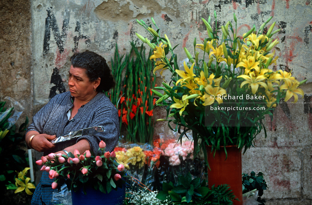 A middle-aged woman florist sells flowers at her stall in Alfama, on 21st March 1994, in Lisbon, Portugal. (Photo by Richard Baker / In Pictures via Getty Images)