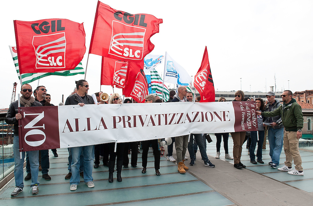 VENICE, ITALY - APRIL 04:  ÊProtesters display a banner against privatizations while passing the Calatrava Bridge on April 4, 2012 in Venice, Italy. Several palaces and historical buildings in Venice have been recently sold by the Municipality or are currently for sale causing local anger.  (Photo by Marco Secchi/Getty Images)