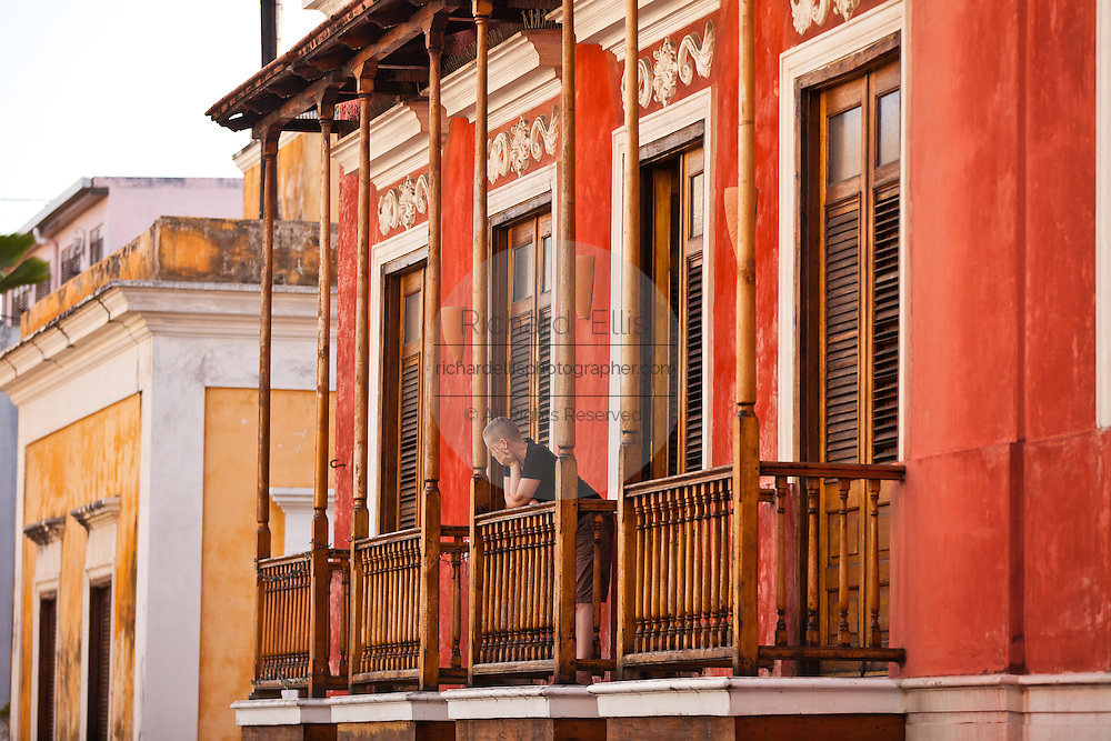 A man looks out from his traditional colonial balcony in Old San Juan, Puerto Rico.