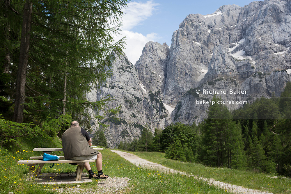 A visitor sits with a mountain vew of Prisank (2,547m) in the Slovenian Julian Alps, on 22nd June 2018, in Triglav National Park, Slovenia.