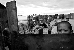 Mongolian children play in a backyard of a makeshift house in Mongolia.