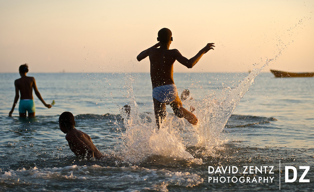 Young pilgrims dash into the water during a sunrise voodou ritual at Bord de Mer de Limonade on the north coast of Haiti on July 25, 2008. After renewing their faith in the mud pit at Plaine du Nord on the days prior, pilgrims migrate to the nearby water, their faith renewed.