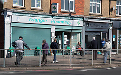 Social distancing queue outside pharmacy during Coronavirus pandemic, Tilehurst, Reading, UK March 2020