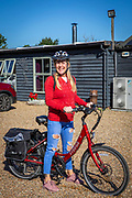 A woman with a red jumper stands with a red electric bike at the UK Electric Bike Centre, Staplehurst, Kent, England, UK.  (photo by Andrew Aitchison / In pictures via Getty Images)