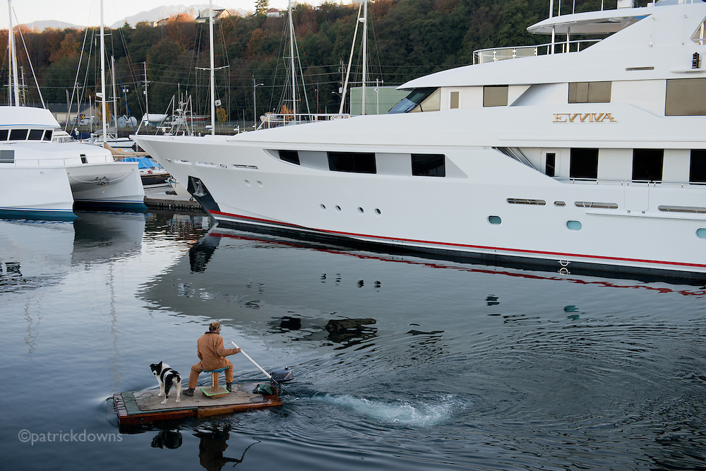 """Tale of two boats: A workman and his faithful dog cruise past the 165 foot yacht """"Evviva"""" in the harbor at Port Angeles."""