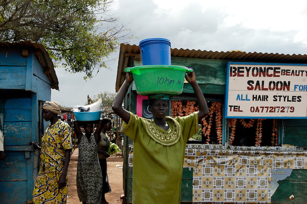 Women pass by the Beyonce beauty salon on market day..Morobo, South Sudan. 08/10/2009..Photo © J.B. Russell