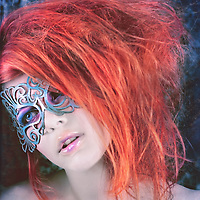 Strange, haunting colorful young woman with attitude wearing an elaborate blue mask
