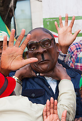 """Lodon, February 21st 2015. Dozens of exiled Zimbabweans gather outside their embassy in London proclaiming Mugabe's last birthday in office. Singing and dancing as they have done every Saturday since 2002, the group spoke with passersby and added yet more names to their petition. PICTURED: As one pair of hands throttles """"Mugabe"""" others make the Movement For Democratic Change's open hand gesture symbolising honesty and integrity, sharply contrasting with the Mugabe regime's culture of corruption."""