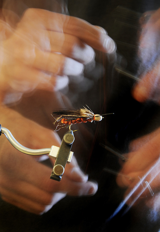 A fly fisherman adds the final wraps of a salmon fly.