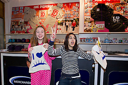 © Licensed to London News Pictures. 28/03/2013. London, UK. One Direction fans Jenny Snell (L) and Ifrah Arif are seen with merchandise after completing a 'supermarket sweep' style rush through the 'One Direction World' pop-up shop which opened today (28/03/2013) at the O2 dome in Greenwich London today. Photo credit: Matt Cetti-Roberts/LNP