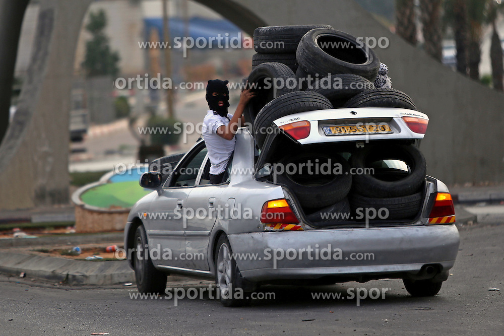 19.10.2015, Ramallah, PSE, Nahostkonflikt zwischen Israel und Pal&auml;stina, im Bild Zusammenst&ouml;sse zwischen Pal&auml;stinensischen Demonstranten und Israelischen Sicherheitskr&auml;fte // A masked Palestinian protester helps carry tyres during clashes with Israeli borderguards next to the Jewish settlement of Beit El. More than two weeks of unrest have raised warnings of the risk of a full-scale Palestinian uprising, while some Israeli politicians have urged residents to arm themselves to fend off the threat of stabbings and gun assaults, Palestine on 2015/10/19. EXPA Pictures &copy; 2015, PhotoCredit: EXPA/ APAimages/ Shadi Hatem<br /> <br /> *****ATTENTION - for AUT, GER, SUI, ITA, POL, CRO, SRB only*****
