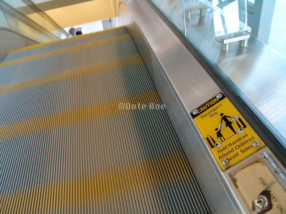 A warning sign to take caution when riding the escalator with a child.