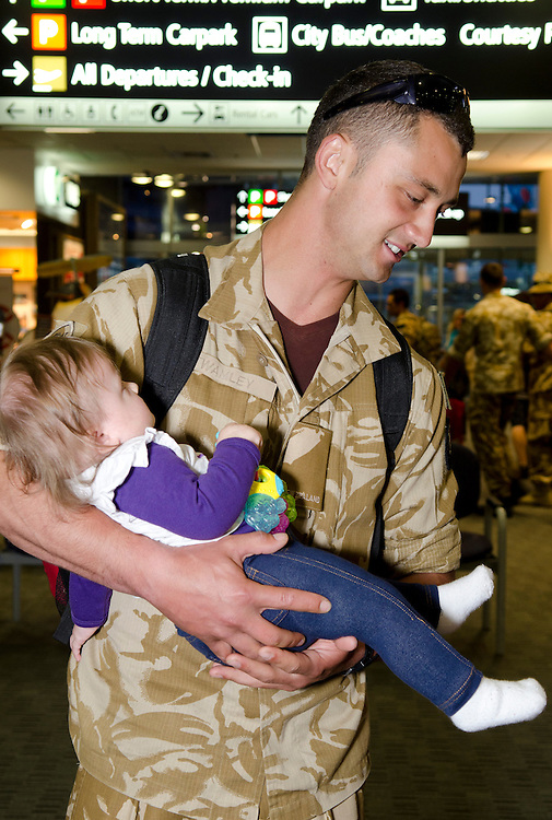 Private Corey Twamley holds daughter Alex, (who was five days old when he left six months ago), on his arrival with the return of the last group of NZ Defence Force personnel who served with the New Zealand Provincial Reconstruction Team (NZPRT) in Bamyan Province, Afghanistan, at Christchurch International Airport, Christchurch, New Zealand, Saturday April 20, 2013. Credit:  SNPA / David Alexander