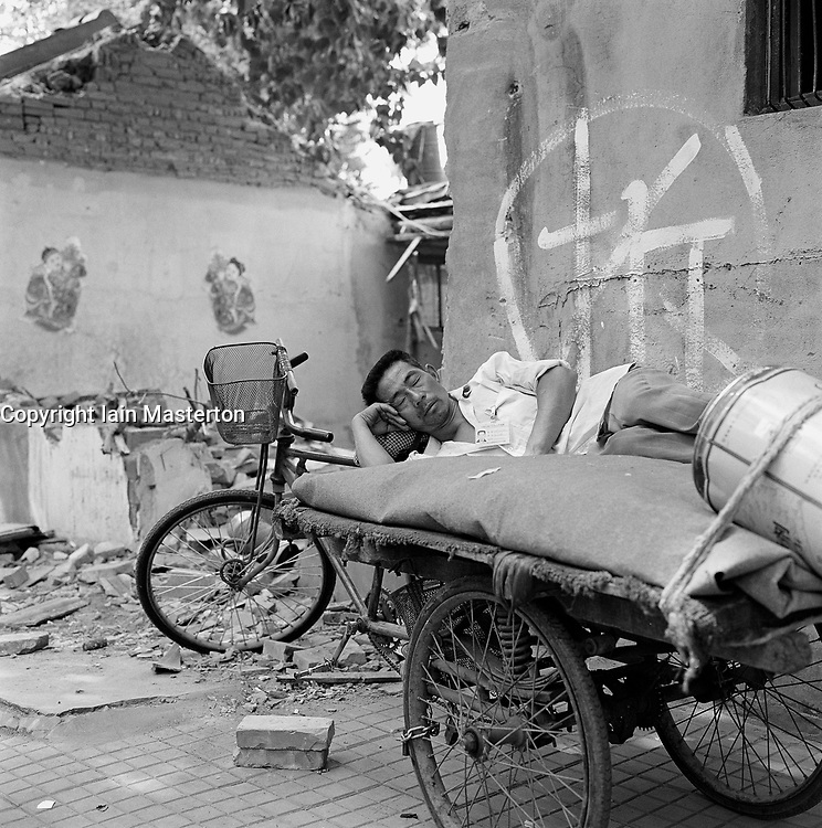 Man sleeping next to house being demolished in Beijing China