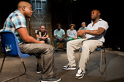 "© Copyright licensed to London News Pictures. 12/11/2010. ""Inside"" by Philip Osment, presented by Playing Out at the Roundhouse, Camden, London. Based on the real experiences of young fathers in prison, the play deals with big questions surrounding relationships, both with their own fathers and with their children. Front L to R: Andre Skeete, Segun Olaiya. Back L to R: Jim Pope, Michael Amaning, Tarkan Cetinkaya, Jacob James Beswick."