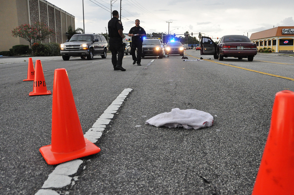 Andrew Knapp, FLORIDA TODAY -- June 24, 2011 -- Police officers work at the scene where a critically injured shooting victim spilled out of a car and onto U.S. 1 just north of Eau Gallie Boulevard, where passers-by performed CPR on the man during rush hour Friday.