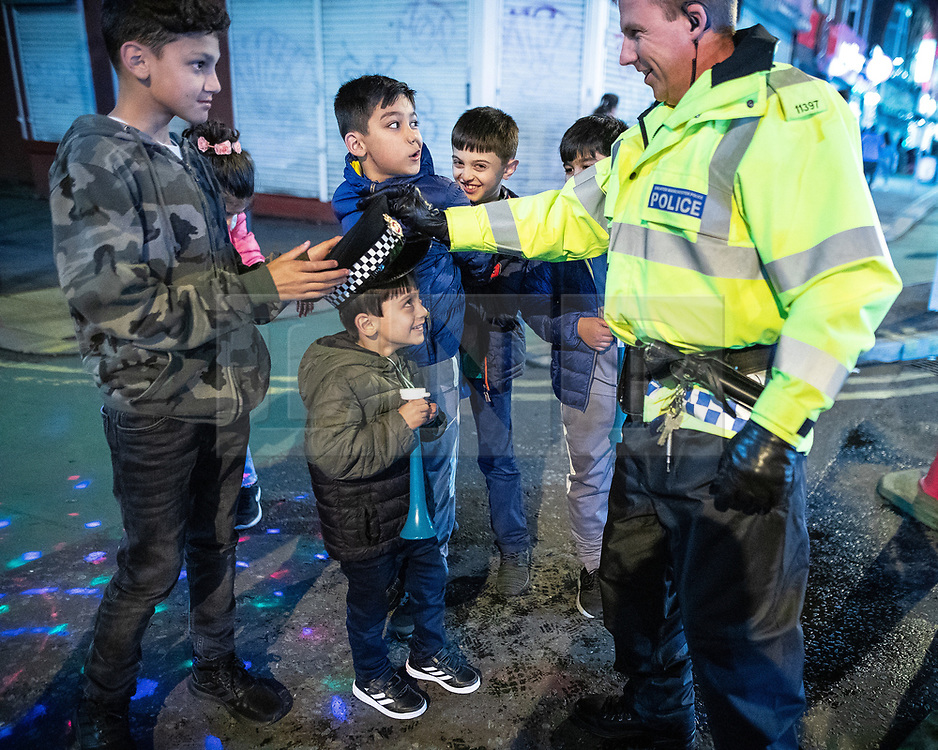 © Licensed to London News Pictures. 05/06/2019. Manchester, UK. A boy tries on a policeman's hat . People celebrate Eid-ul-Fitr , the end of a month of fasting during Ramadan , in Rusholme in Manchester . Photo credit: Joel Goodman/LNP